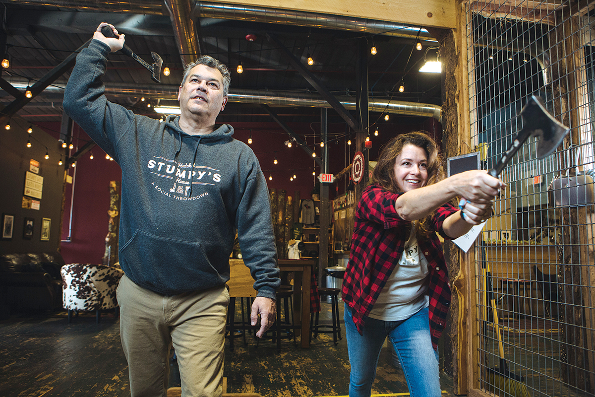 THROWING DOWN: Bryan and Kim Besse, owners of Stumpy's Hatchet House in Fall River, toss hatchets in one of the business's eight throwing pits. Kim Besse says the hatchet-throwing entertainment business hosts single participants, parties and corporate events. /PBN PHOTO/RUPERT WHITELEY