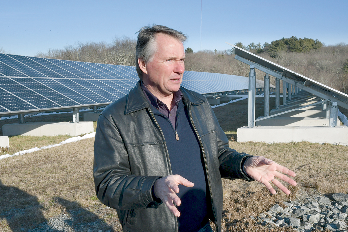 BEST OF BOTH WORLDS: David Lamb, assistant director of facilities services and utilities for the University of Rhode Island, at a solar array built on the former West Kingston landfill site in South Kingstown. Lamb says the project is the best of both worlds – development of clean energy that helps the state reduce its reliance on fossil fuels without sacrificing the carbon absorption and wildlife habitat benefits of trees. / PBN PHOTO/MIKE SKORSKI