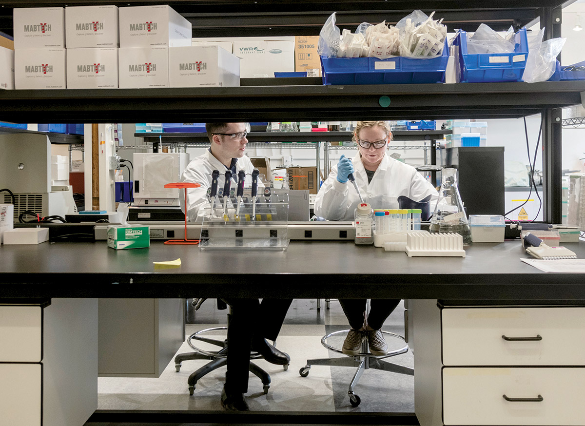 LAB WORK: Research associates Mitchell McAlister and Olivia Morin work in the lab at EpiVax in Providence. The biotechnology company recently began working on a coronavirus vaccine. / PBN PHOTO/MICHAEL SALERNO