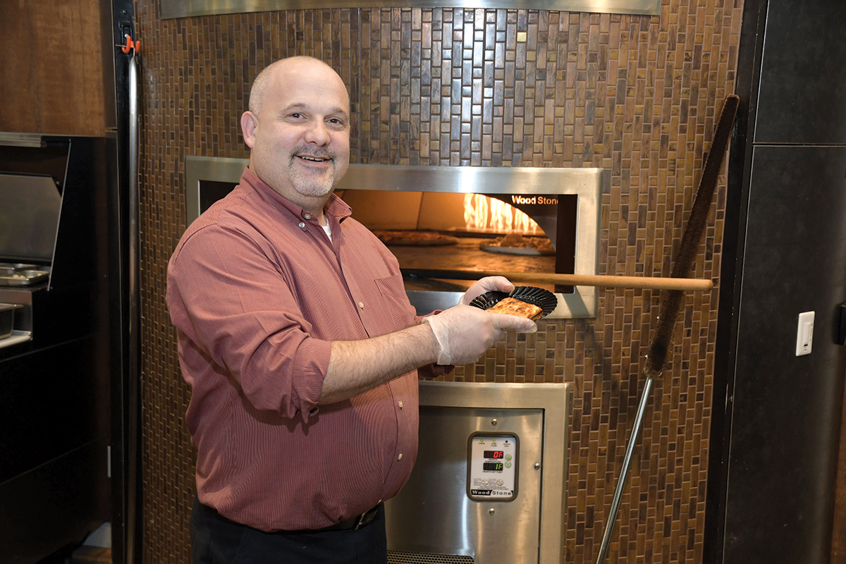 ADDED BENEFIT: Luis Melo, a chef in the campus cafeteria at the Citizens Bank headquarters complex in Johnston, takes pizza out of the oven. The oven is one of several amenities the bank has included at the campus to help retain current employees and recruit new ones. / PBN PHOTO/MIKE SKORSKI