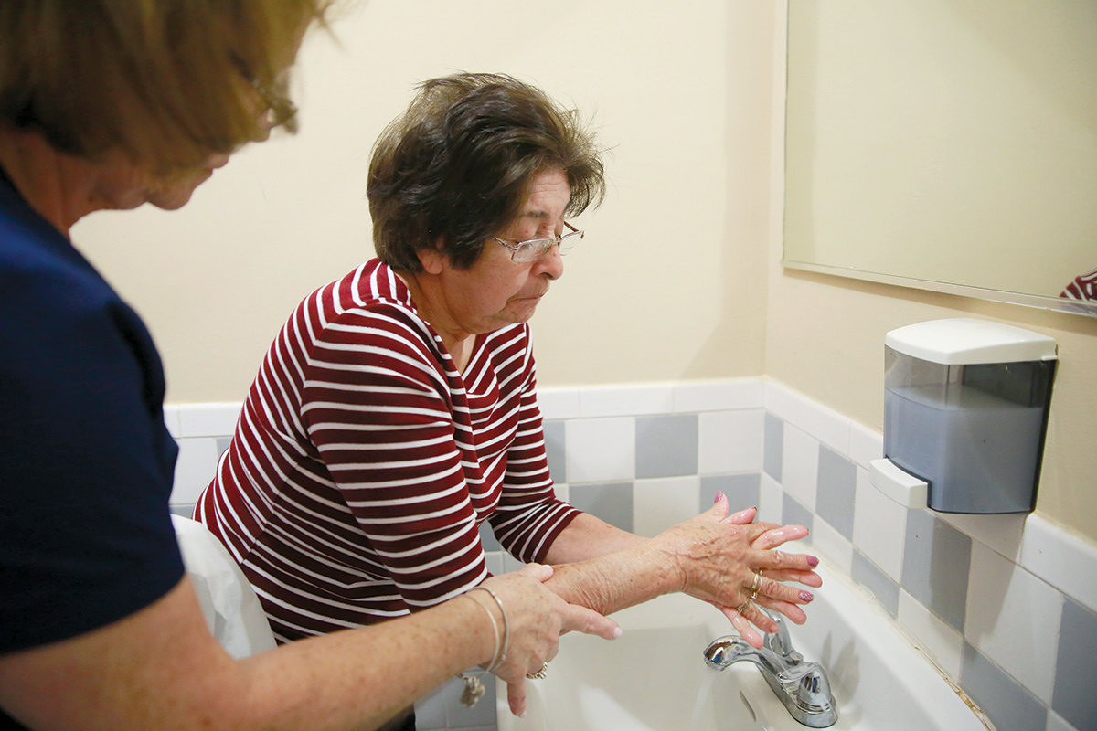 HELPING HAND: Nursing home resident Maria Castro receives assistance in  washing her hands from nurse Maria Casal Hernandez, left, at the Little Havana Activities and Nutrition Centers of Dade County Inc. in Miami. / AP PHOTO/BRYNN ANDERSON