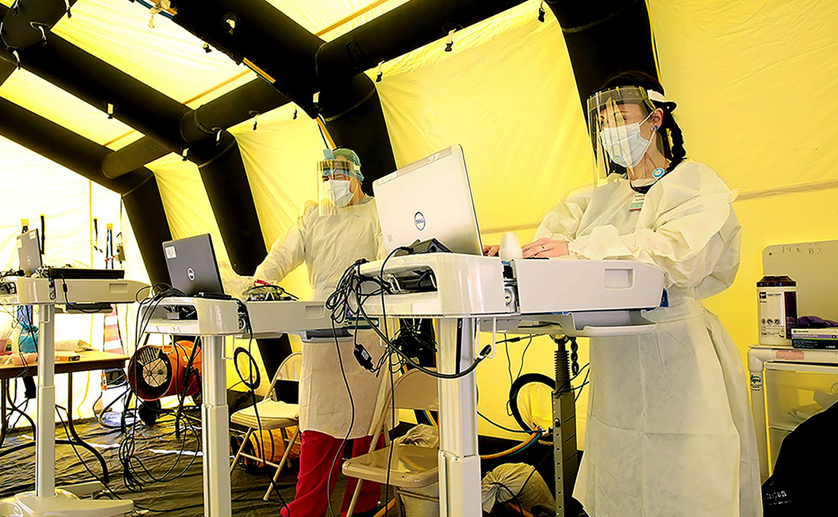 FRONT LINES: Health workers type on laptops inside a COVID-19 patient tent set up outside the emergency department at Rhode Island Hospital in Providence. / COURTESY LIFESPAN CORP.