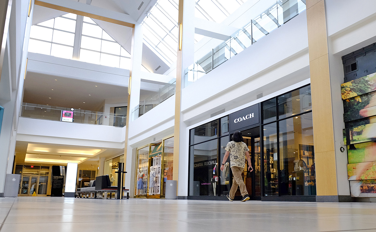 LONELY PLACE: A visitor walks in an empty hallway at The Fashion Mall at Keystone in Indianapolis in March. Some corporations are taking the first steps toward bringing employees back to work. / AP FILE PHOTO/DARRON CUMMINGS